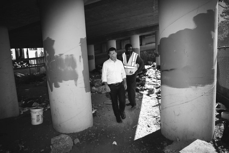 Image:  Sam Dodge, left, the Director of the Mayor's Office of HOPE, and Jonathan Gomwalk, a Community Liason for Homeless Outreach for Public Works, tour an area under an overpass which used to be a homeless encampment in San Francisco