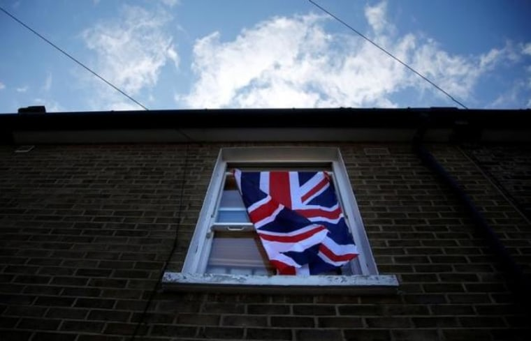 A British flag flutters in front of a window in London,