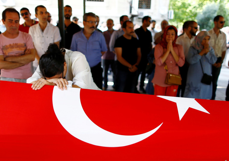 Image: A relative of a victim of Tuesday's attack on Ataturk airport mourns at her flag-draped coffin during her funeral ceremony in Istanbul