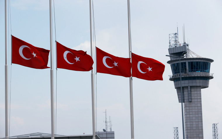 Image: Turkish flags, with the control tower in the background, fly at half mast at the country's largest airport, Istanbul Ataturk, following yesterday's blast in Istanbul