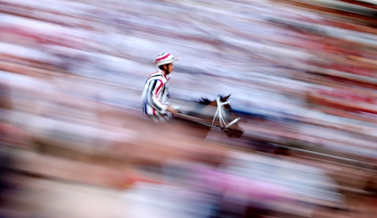 "Image: Jockey Elias Mannucci of ""Istrice"" (Porcupine) parish rides his horse during the first practice for the Palio horse race in Siena"