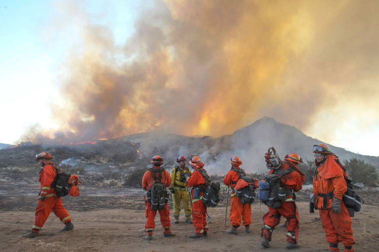 Firefighters are briefed on their duties as a backfire burns at the 6,500 acre Border Fire in eastern San Diego County, California, in the late afternoon on June 22.