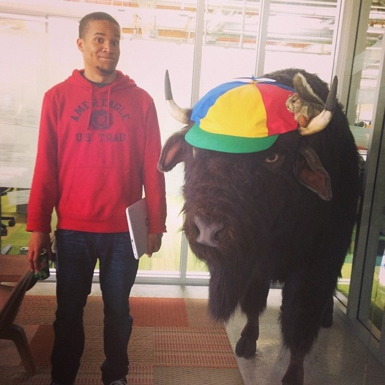 Howard University student Chris Horcutt poses with a bison during his internship after his first year with the GIR program.
