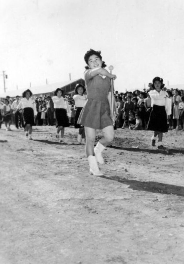 Patsy Yorita performing a flag salute at the Tule Lake concentration camp at the Independence Day parade. (1943)