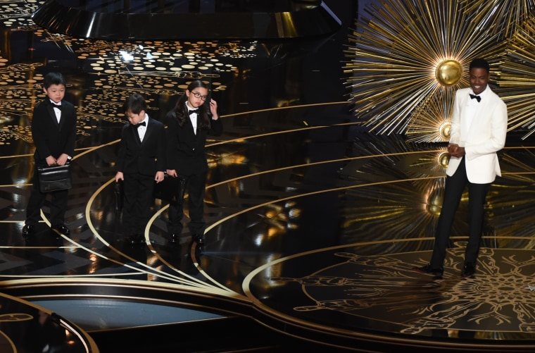 Chris Rock and three children representing accountants at the 88th Academy Awards.