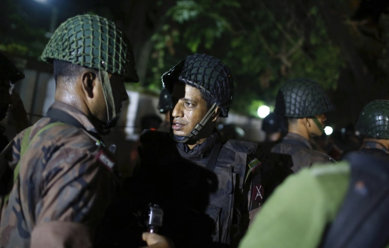 Image: Bangladeshi security personnel stand guard near a restaurant that has reportedly been attacked by unidentified gunmen in Dhaka