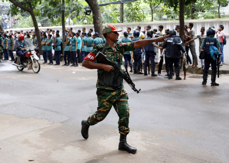 Image: A security personnel reacts near the Holey Artisan restaurant after gunmen attacked the upscale cafe, in Dhaka