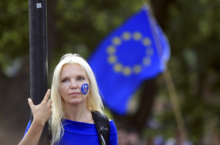 Image: A woman stands still during a demonstration against Britain's decision to leave the European Union, in central London