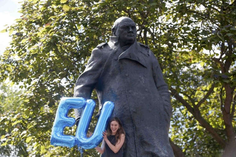 Image: A woman holds an EU balloon tied to the Winston Churchill statue in Parliament Square during a demonstration against Britain's decision to leave the European Union, in central London