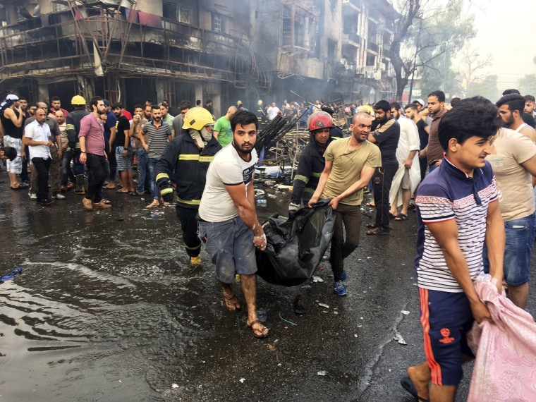 Image: Iraqi firefighters and civilians carry bodies of victims killed in a car bomb at a commercial area in in Baghdad