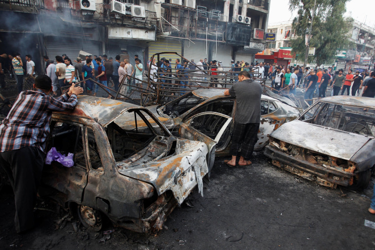 Image: People inspect the site of a suicide car bomb in the Karrada shopping area, in Baghdad