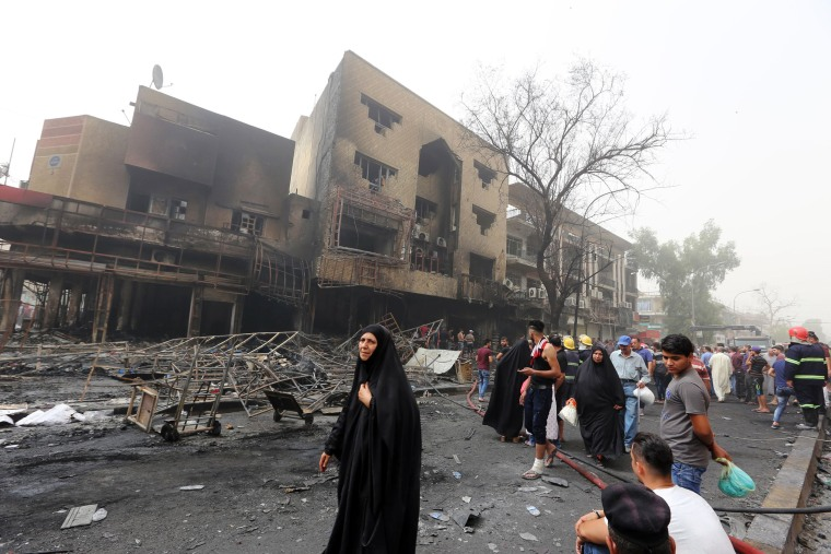 Image: Iraqis, including firefighters, gather at the site of a suicide car bombing