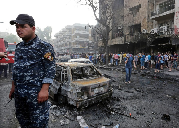 Image: Iraqis gather at the site of suicide bomb attack in the Karada