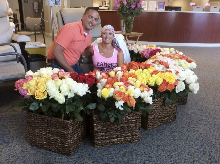 Image: Brad Bousquet and his wife, Alissa, sit by the 500 roses he presented to her