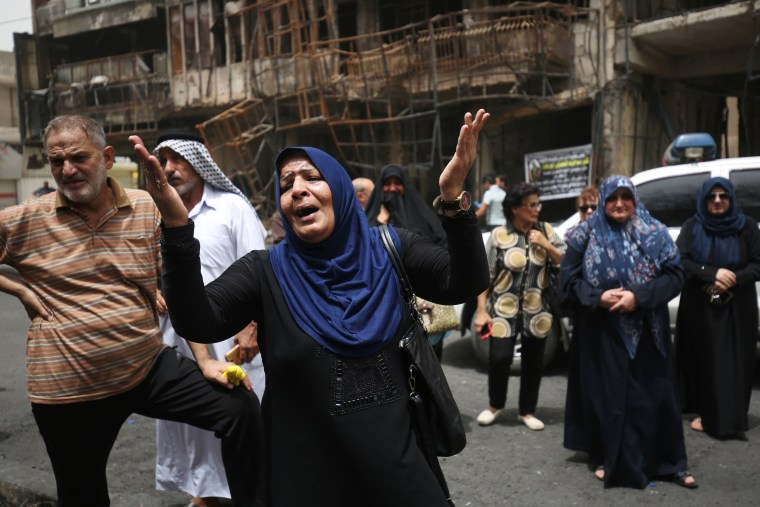Image: Iraqis react at the site of a suicide-bombing attack