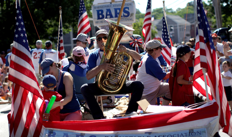 Image: A man plays a horn as he rides a float through Barnstable Village, on Cape Cod during July 4th parade