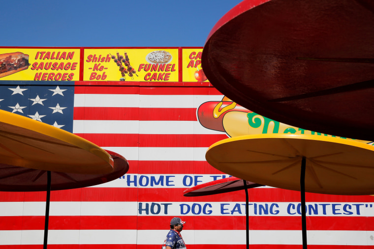 Image: A man dressed in American colors walks through a dining area before Nathan's Famous Fourth of July International Hot Dog-Eating Contest at Coney Island in Brooklyn, New York