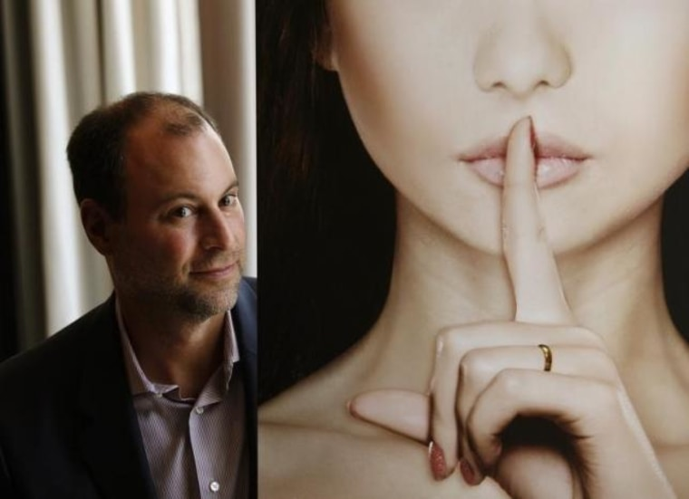 Ashley Madison founder Noel Biderman poses with a poster during an interview in Hong Kong