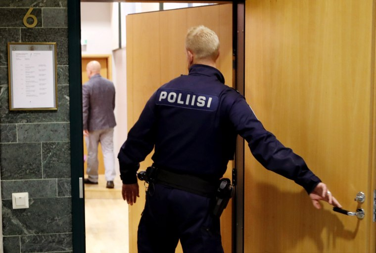Image: A police officer is photographed at the Pirkanmaa district court where a hearing for the case of six Cuban volleyball players suspected of an aggravated rape takes place in Tampere