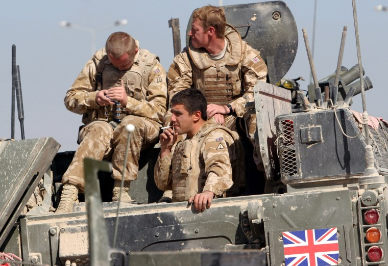 Image: British army soldiers on top of an armored vehicle