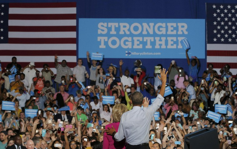 Image: U.S. President Obama puts his hand on the back of U.S. Democratic presidential candidate Clinton as they wave to the crowd together during a Clinton campaign rally in Charlotte