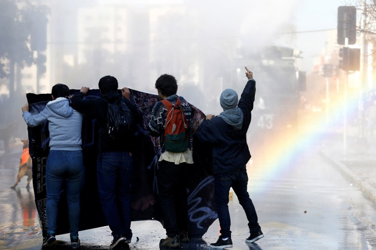 Image: Demonstrators clash with riot policemen during an unauthorized march called by the Chilean student federations to protest against government's education reform, in Santiago
