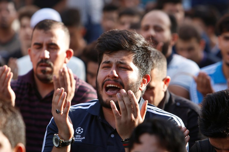 Image: Sunni and Shi'ite Muslims attend prayers during Eid al-Fitr at the site of a suicide car bomb attack over the weekend at the shopping area of Karrada, in Baghdad