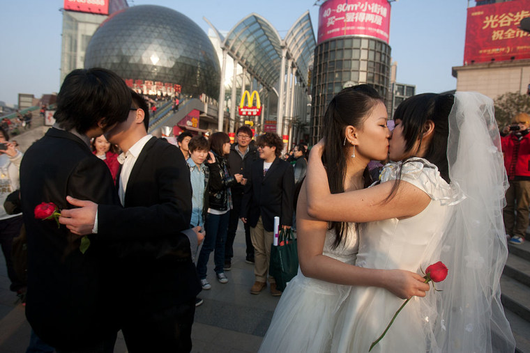 Gay couples kiss during their ceremonial 'wedding' as they try to raise awareness of the issue of same-sex marriage, in Wuhan, in central China's Hubei province on March 8, 2011.