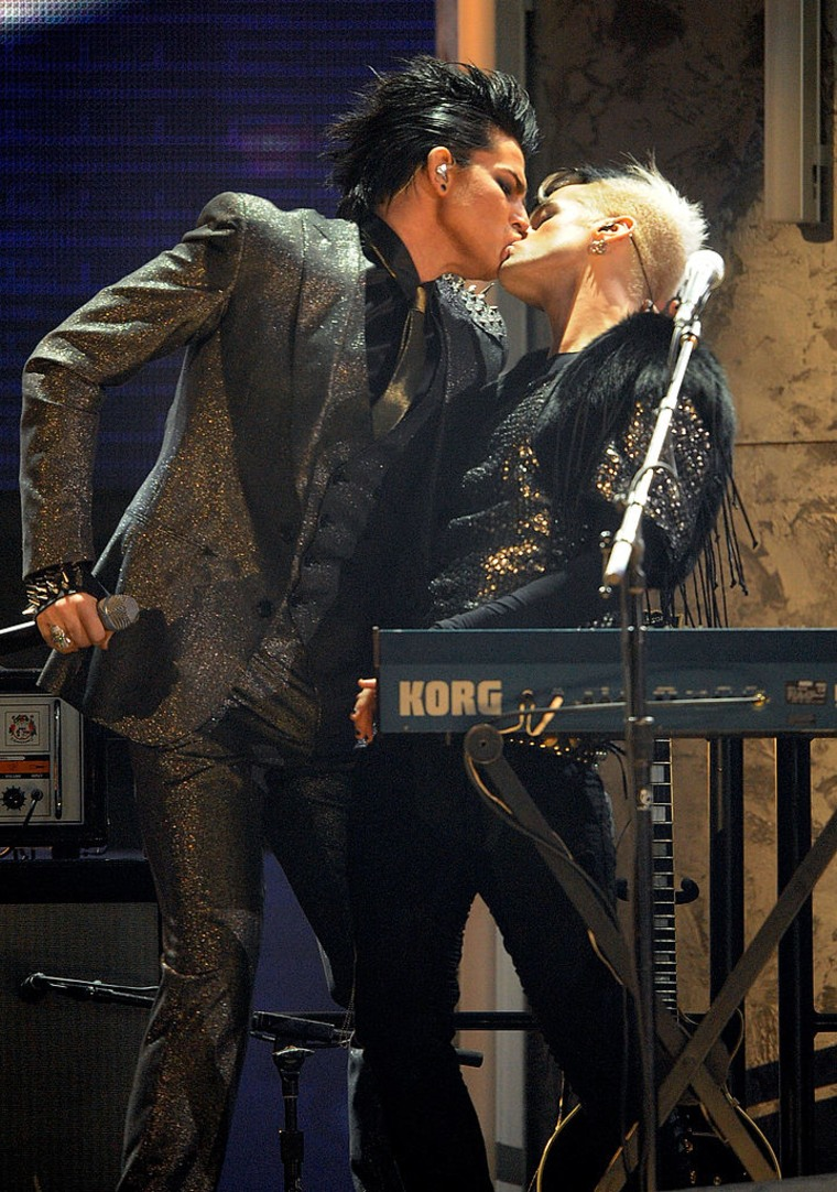 Singer Adam Lambert (L) and a musician kiss onstage at the 2009 American Music Awards at Nokia Theatre L.A.