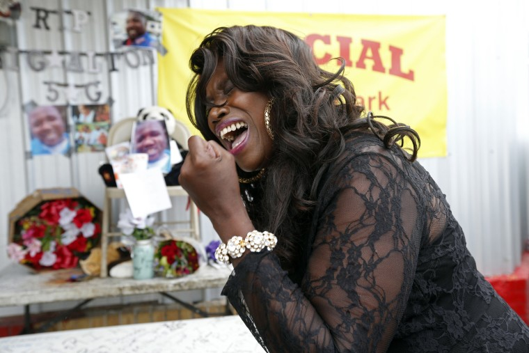 Image: Stephanie McDee sings a song and protests at a makeshift memorial for Alton Sterling