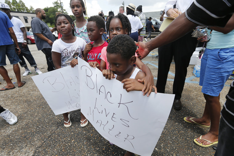 "Image: Children hold signs reading ""Black Lives Matter"" outside the Triple S convenience store in Baton Rouge"