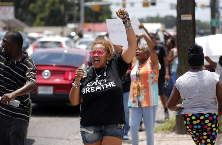 Image: People march outside the Triple S convenience store in Baton Rouge