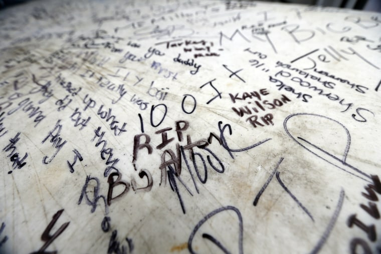 Image: Messages of condolence are written on a table at a makeshift memorial for Alton Sterling