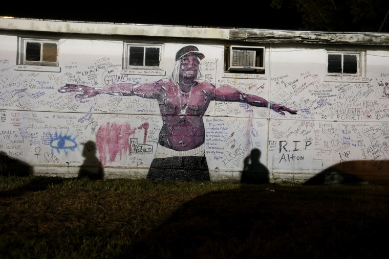 Image: Shadows fall on a newly painted mural of Alton Sterling