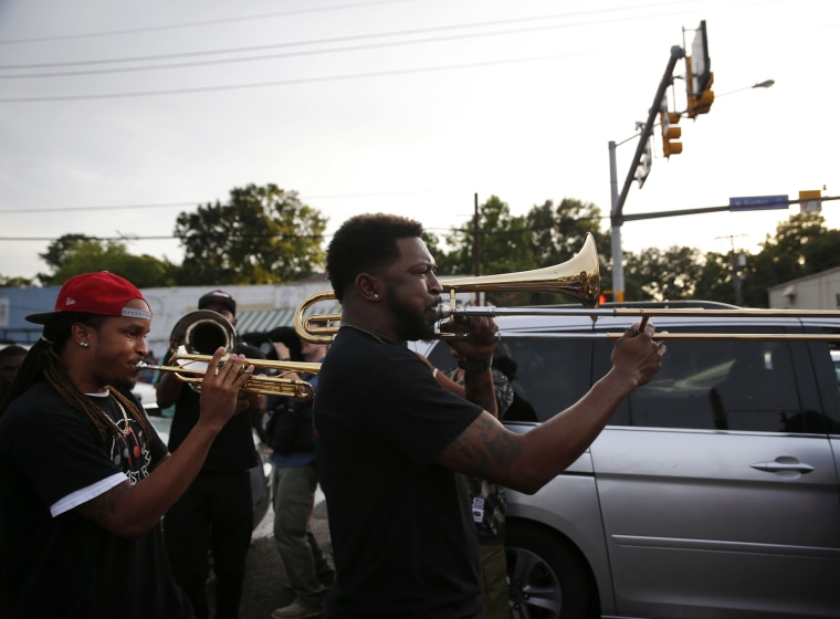 Image: A brass band marches through the street after a vigil for Alton Sterling
