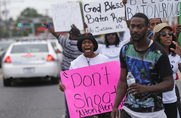 Image: People demonstrate in the street as police cars pass outside the Triple S convenience store in Baton Rouge