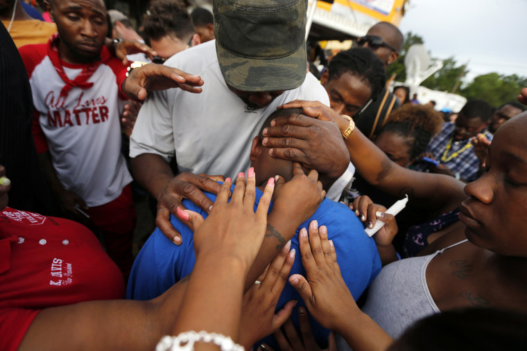 Image: Cameron Sterling, son of Alton Sterling, is comforted by hands from the crowd at a vigil