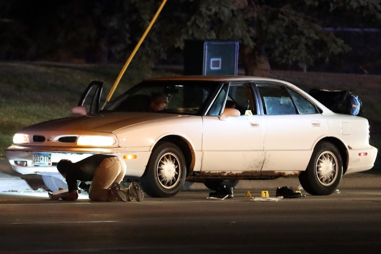 Image: Investigators search a car at the scene of a police involved shooting
