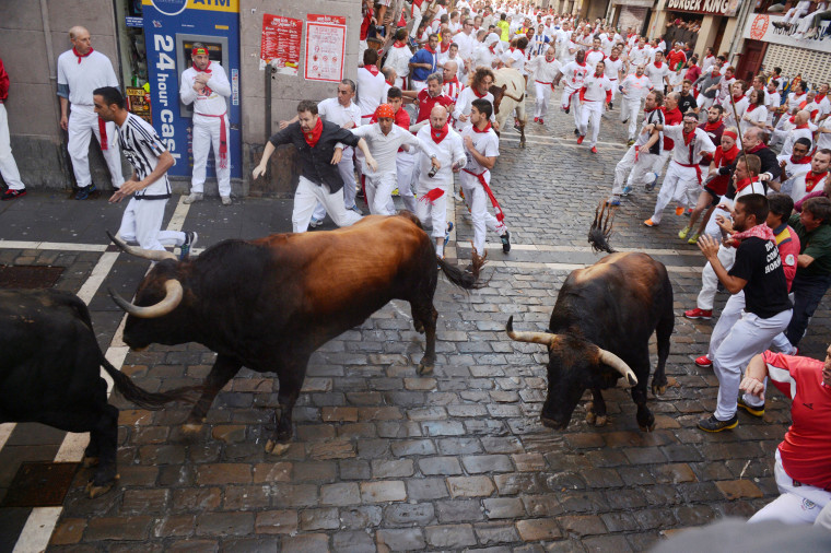 Image: Fuente Ymbro fighting bulls take the Estafeta corner during the first running of the bulls at the San Fermin festival in Pamplona