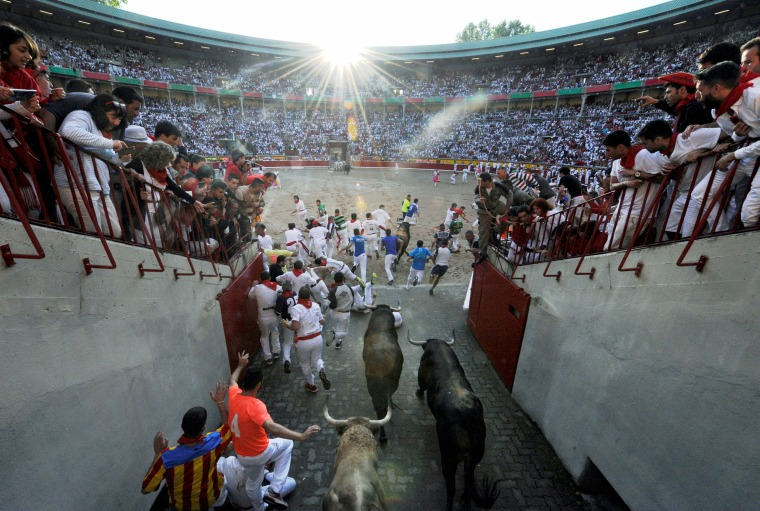 Image: Runners sprint alongside Fuente Ymbro fighting bulls at the entrance to the bullring during the first running of the bulls at the San Fermin festival in Pamplona
