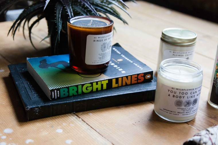 "Tanwi Nandini Islam's novel ""Bright Lines"" next to Hi Wildflower Botanica's candles"