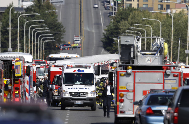 A Ride the Ducks tour bus that was involved in a crash with several other vehicles can be seen behind an ambulance as officials respond, Thursday, Sept. 24, 2015 in Seattle. Seattle fire officials say two people have been killed and numerous others critic