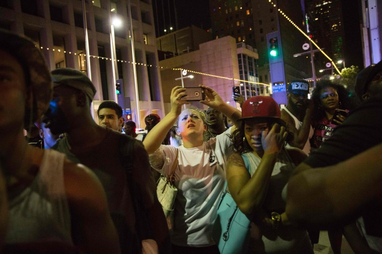 Protestors yell after police officers arrest a bystander following the shooting at a protest in Dallas