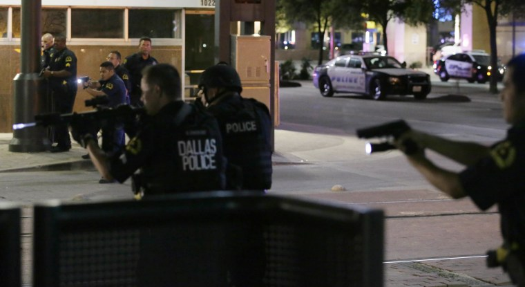 Image: Dallas police move to detain a driver after several police officers were shot in downtown Dallas