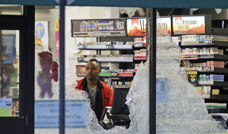 Image: A clerk looks at broke windows shot out at a store in downtown Dallas