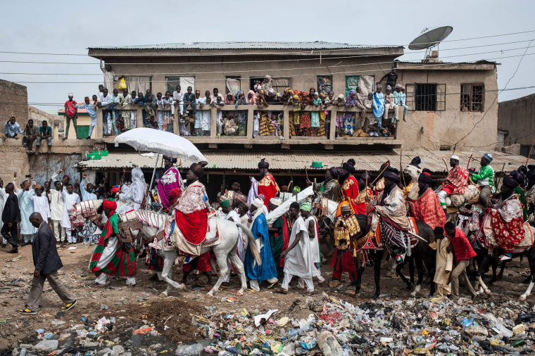 Image: The Emir of Kano rides a horse as he parades with his entourage and musicians on the streets of Kano