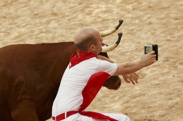 Image: A reveler is tossed as he tries to get a snapshot next to a bull