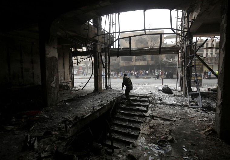 Image: An Iraqi man searches for bodies of victims inside a building damaged by a suicide-bombing attack in Baghdad