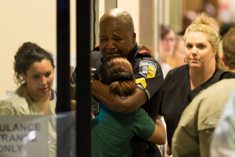Image: A DART police officer receives comfort at Baylor University Hospital emergency room entrance after a shooting attack in Dallas