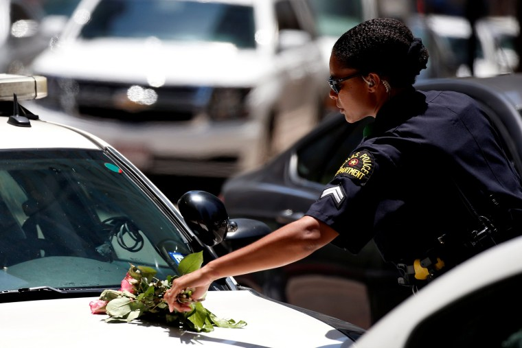 Image: A Dallas police officer picks up a bouquet of flowers from the hood of her car following a prayer vigil